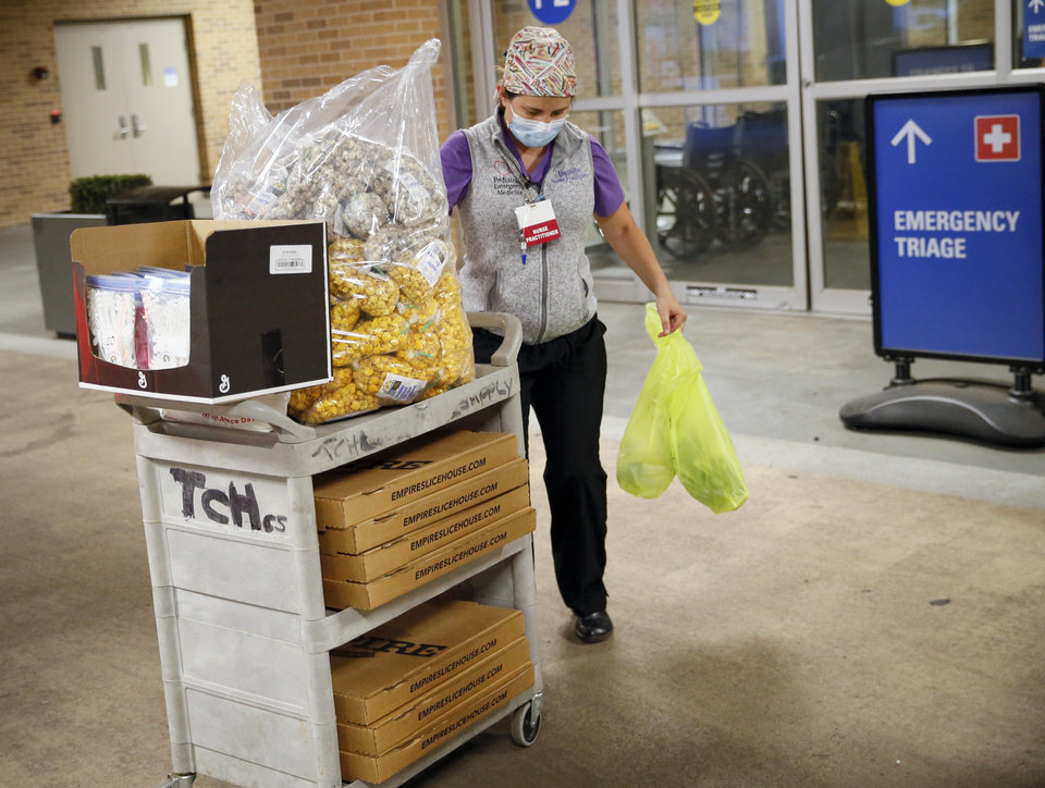 Photo - Nurse practitioner Danielle Briseno takes a cart of pizza, popcorn and healthcare mask extender straps into the emergency room at The Children's Hospital in Oklahoma City, Sunday, April 26, 2020. Oklahoma's Credit Union purchased pizza from Empire Slice House and popcorn from Oklahoma Gourmet Popcorn for a popcorn and pizza party for night shift healthcare workers at the emergency room. The hospital also received healthcare mask extenders manufactured by entrepreneurs Ian and Hailey McDermid, owners of The Pump Bar and The Bunker Club. [Nate Billings/The Oklahoman]