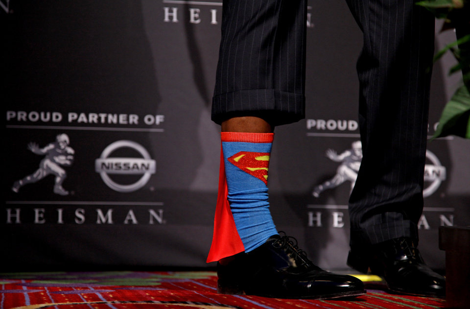 Photo -  Heisman Trophy winner Robert Griffin III, of Baylor, shows off his Superman socks during a news conference after the ceremony, Saturday, Dec. 10, 2011, in New York. The junior quarterback known as RG3 became the first Heisman winner from Baylor. (AP Photo/Craig Ruttle) ORG XMIT: NYCR118