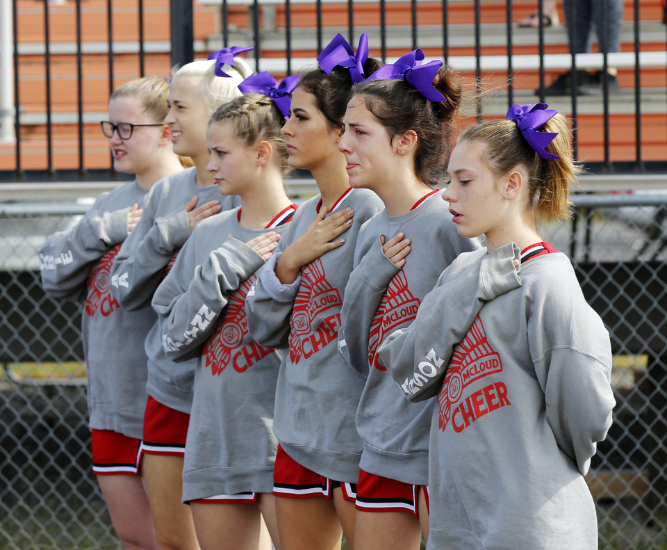 Photo - The McLoud cheerleaders stand during the national anthem before a high school football game between McLoud and Cushing at O'Dell Field in Cushing, Okla., Saturday, Oct. 6, 2018. The game was postponed and moved from McLoud after Kaylen Thomas, a McLoud High School student, was fatally shot the previous day. The cheerleaders wore purple bows because they said purple was Thomas' favorite color. Photo by Nate Billings, The Oklahoman