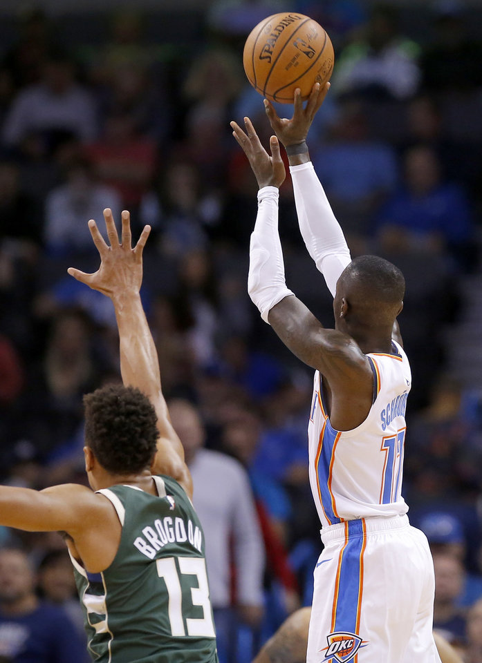 Photo - Oklahoma City's Dennis Schroder (17) shoots over Milwaukee's Malcolm Brogdon (13) during a NBA preseason game between the Oklahoma City Thunder and Milwaukee Bucks at Chesapeake Energy Arena in Oklahoma City,  Tuesday, Oct. 9, 2018. Photo by Sarah Phipps, The Oklahoman