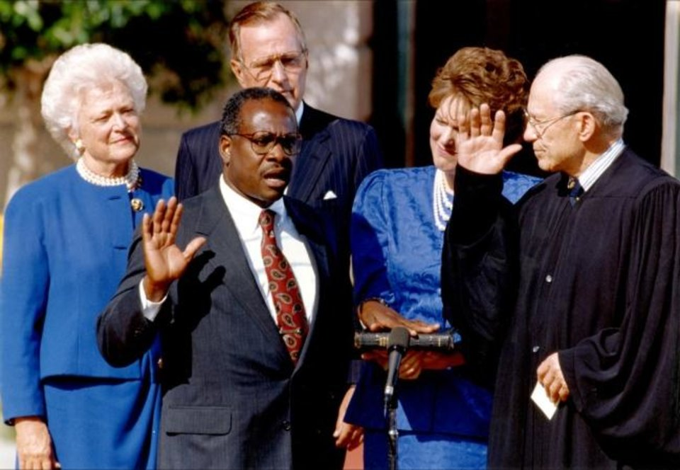 Photo -  Clarence Thomas is sworn in to the Supreme Court by Justice Byron White, while Thomas' wife, Virginia, center, Barbara Bush and President George H.W. Bush look on. [Photo provided by Justice Clarence Thomas]