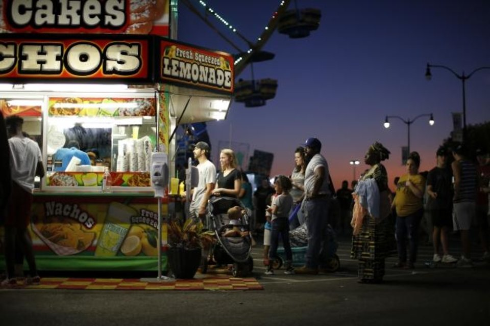 Photo -  Fairgoers wait in line for food Tuesday night at the OKC Fairgrounds. [Bryan Terry/The Oklahoman]