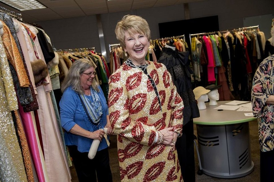 Photo - The University of Central Oklahoma in 2017 received a $6,000 grant from the National Endowment for the Humanities to help preserve UCO's historic fashion collection. From left, UCO Grants Coordinator Mary Huffman, helps Kaye Sears, head of the department of Human Environmental Sciences, who is modeling a 1960s sequined coat. [Photo provided]