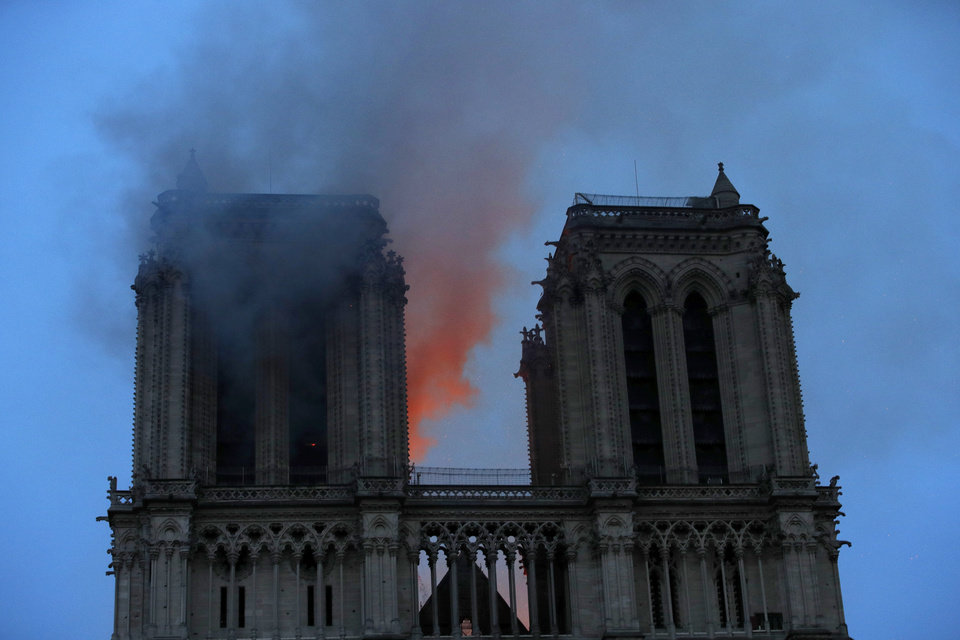 Photo - Smoke and flames fill the sky as a fire burns at the Notre Dame Cathedral during the visit by French President Emmanuel Macron in Paris, Monday, April 15, 2019. A catastrophic fire engulfed the upper reaches of Paris' soaring Notre Dame Cathedral as it was undergoing renovations Monday, threatening one of the greatest architectural treasures of the Western world as tourists and Parisians looked on aghast from the streets below.(Philippe Wojazer/Pool via AP)