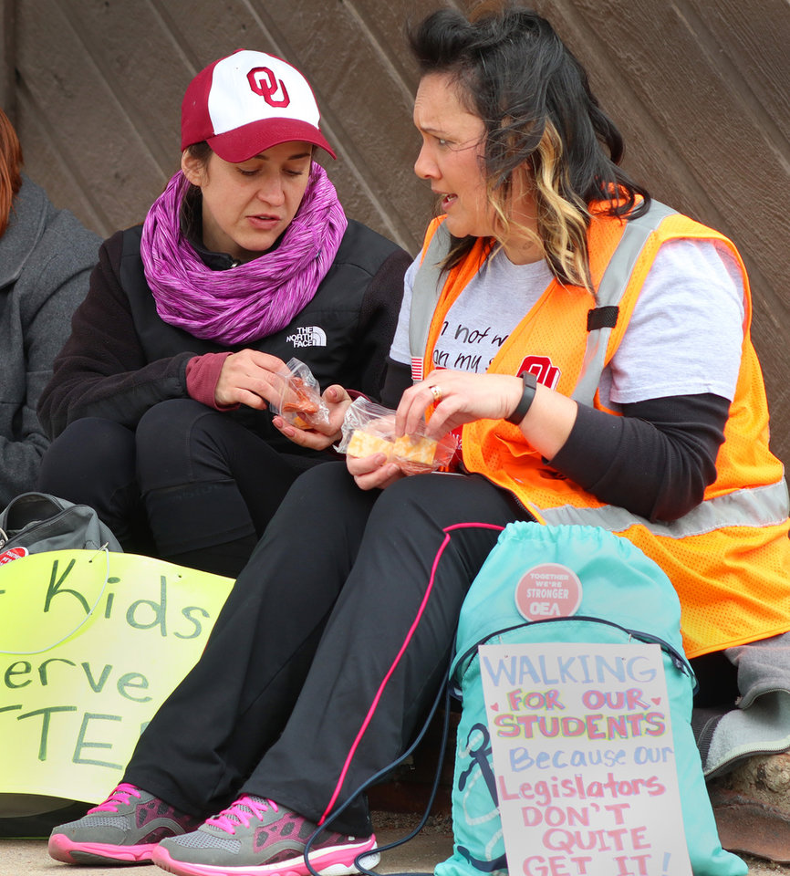 Photo - Teachers from MacArthur Elementary Elizabeth Beard, left, and Shantel Price eat snacks while stopped at Turk's Country store during the March for Public Education by Tulsa teachers, students and supporters, who are walking to the Capitol from Tulsa along SH 66, Sunday, April 8, 2018. Photo by Doug Hoke, The Oklahoman