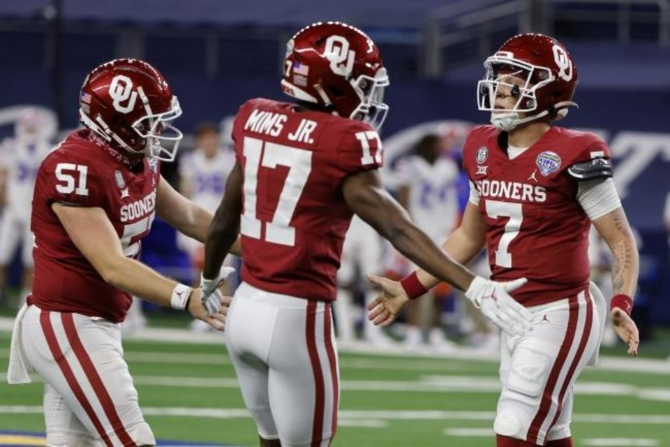 Photo -  Oklahoma long snapper Kasey Kelleher (51) and wide receiver Marvin Mims (17) celebrate with quarterback Spencer Rattler, right, after Ratthler carried the ball for a touchdown in the first half of the Cotton Bowl NCAA college football game against Florida in Arlington, Texas, Wednesday, Dec. 30, 2020. (AP Photo/Michael Ainsworth)