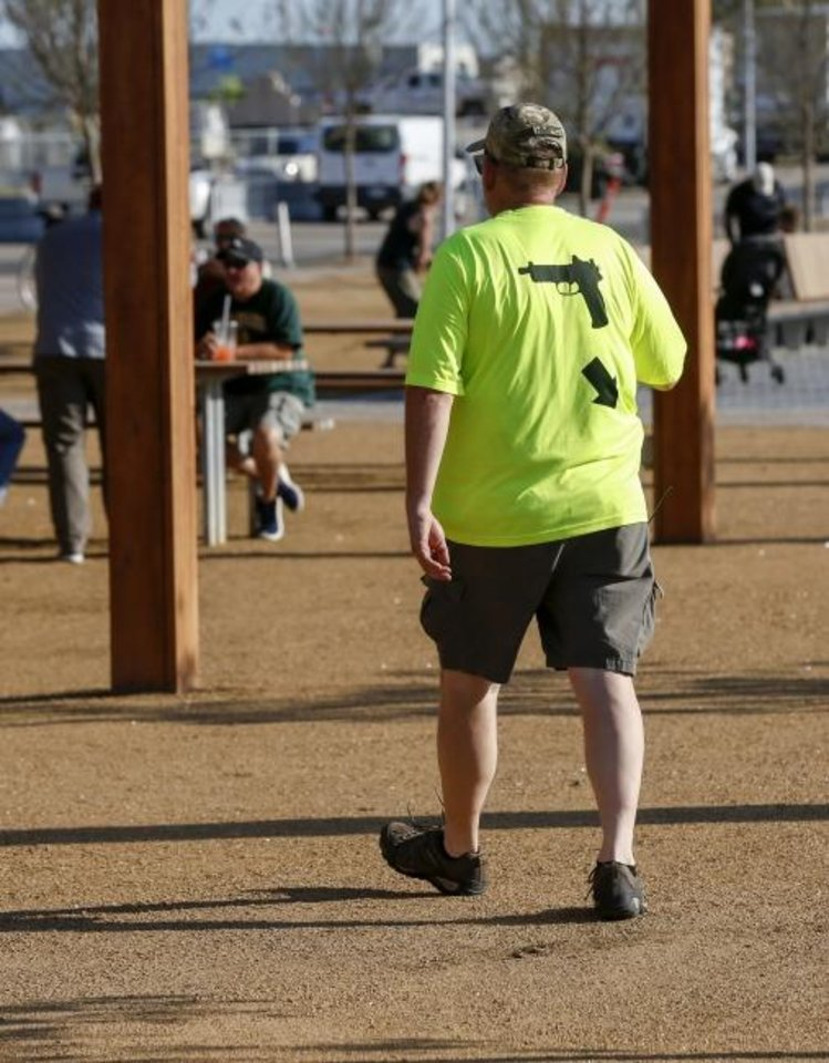 Photo -  A man wears a shirt indicating he is carrying a firearm during the grand opening of Scissortail Park in Oklahoma City. A law allowing most Oklahomans to carry a gun without a permit is to take effect Nov. 1. [Nate Billings/The Oklahoman]