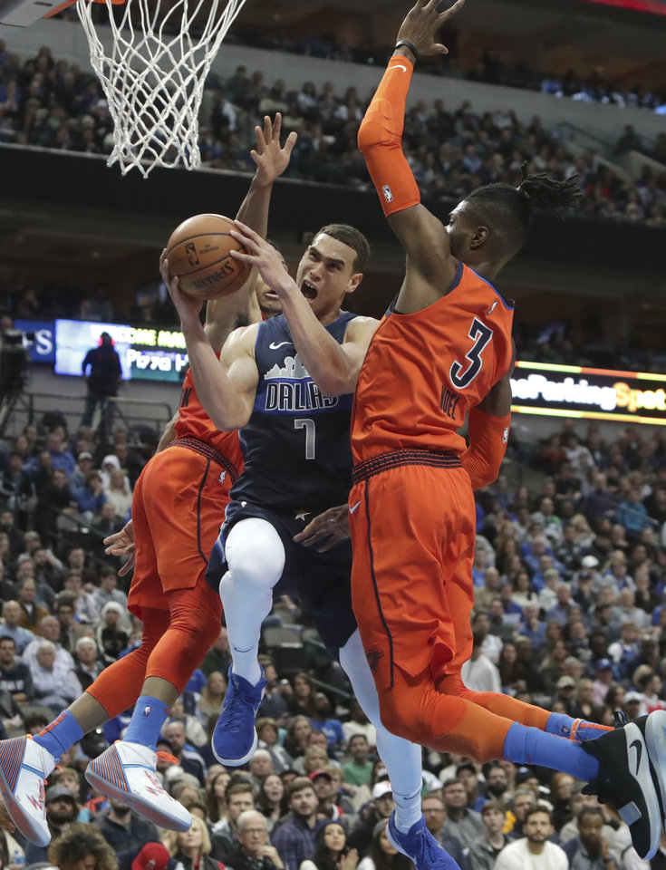 Photo - Dallas Mavericks forward Dwight Powell (7) drives between Oklahoma City Thunder defenders Nerlens Noel (3) and Russell Westbrook (0) during the second half of an NBA basketball game in Dallas, Sunday, Dec. 30, 2018. The Mavericks won 105-103. (AP Photo/LM Otero)