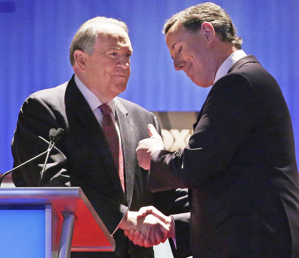 Photo - Republican presidential candidate, former Arkansas Gov. Mike Huckabee, left, shakes hands with Republican presidential candidate, former Pennsylvania Sen. Rick Santorum after the Fox Business Network Republican presidential debate at the North Charleston Coliseum, Thursday, Jan. 14, 2016, in North Charleston, S.C. (AP Photo/Chuck Burton)