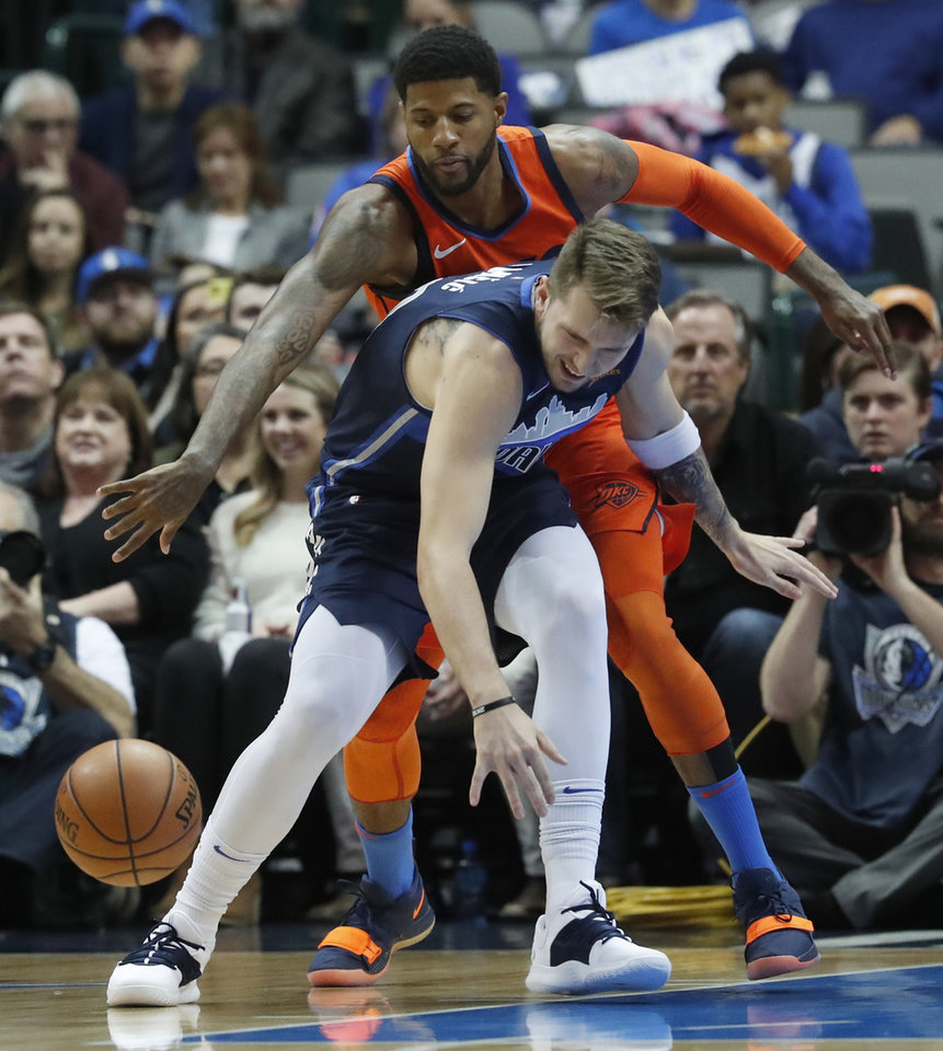 Photo - Oklahoma City Thunder forward Paul George, top, reaches to disrupt the dribble by Dallas Mavericks forward Luka Doncic, of Germany, during the first half of an NBA basketball game in Dallas, Sunday, Dec. 30, 2018. (AP Photo/LM Otero)
