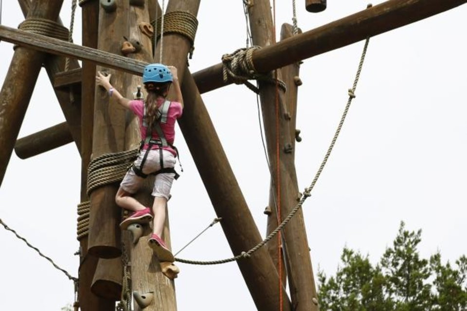 Photo -  Falls Creek youth camper Shylynn climbs the Alpine Tower during afternoon activities on Tuesday at Falls Creek Baptist Conference Center near Davis. [Paxson Haws/The Oklahoman]