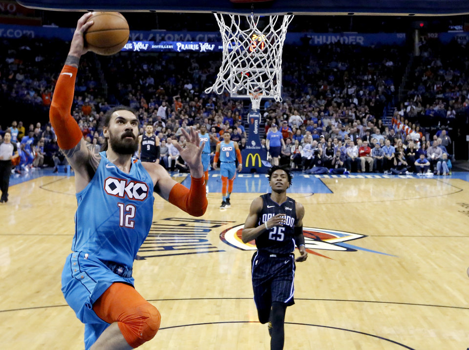 Photo - Oklahoma City's Steven Adams (12) goes up for a lay up in front of Orlando's Wesley Iwundu (25) during the NBA game between the Oklahoma City Thunder and the Orlando Magic at the Chesapeake Energy Arena  Tuesday, Feb. 5, 2019. Photo by Sarah Phipps, The Oklahoman
