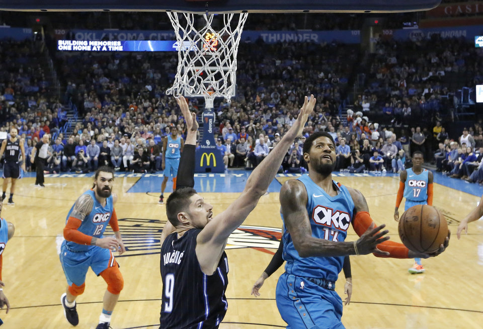 Photo - Oklahoma City's Paul George (13) shoots as Orlando's Nikola Vucevic (9) defends during the NBA game between the Oklahoma City Thunder and the Orlando Magic at the Chesapeake Energy Arena  Tuesday, Feb. 5, 2019. Photo by Sarah Phipps, The Oklahoman