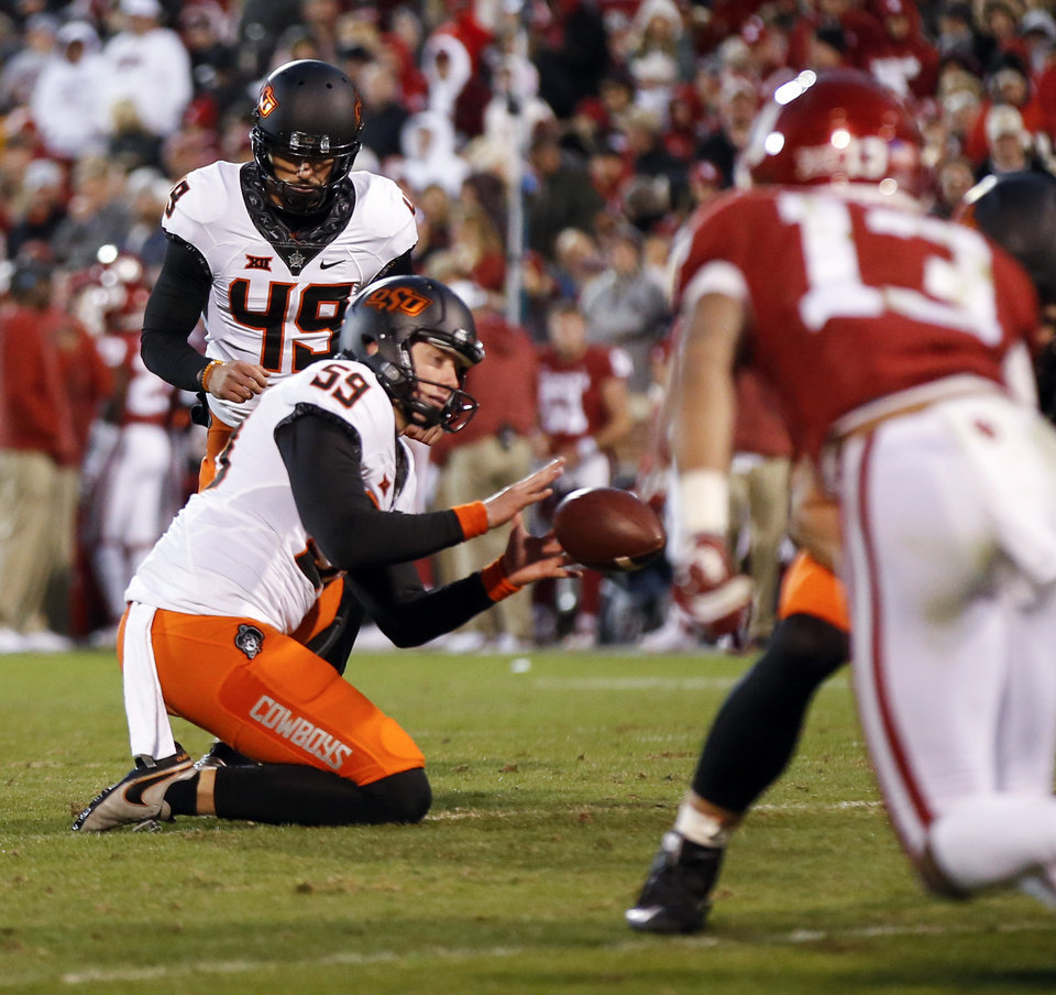 Photo - Oklahoma State's Matt Ammendola (49) attempts an extra point as holds Matt Hockett (59) receives the ball in the fourth quarter during a Bedlam college football game between the University of Oklahoma Sooners (OU) and the Oklahoma State University Cowboys (OSU) at Gaylord Family-Oklahoma Memorial Stadium in Norman, Okla., Nov. 10, 2018. Ammendola missed the extra point. OU won 48-47. Photo by Nate Billings, The Oklahoman