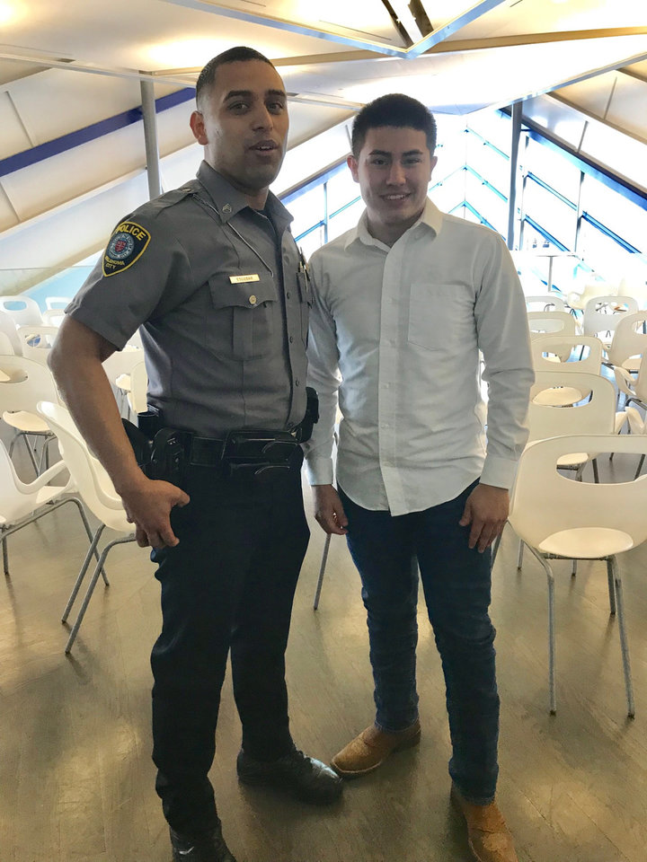 Photo -  Oklahoma City police Sgt. Tony Escobar poses for a picture with Ismael Gonzalez after Gonzalez graduated from the police department's Juvenile Intervention Program during a ceremony at the Devon Boathouse. [Photo by Carla Hinton, The Oklahoman]