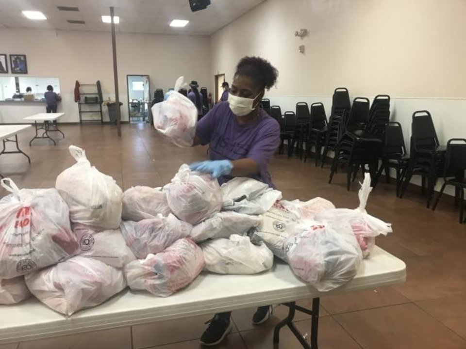 Photo -  Volunteer Deneen Reed puts sacks of meat on a table before they are distributed to families as part of the Fishes and Loaves drive-thru food distribution at  Fairview Missionary Baptist Church, 1700 NE 7. [Carla Hinton/The Oklahoman]