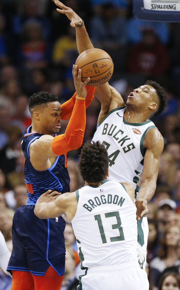 Photo - Oklahoma City's Russell Westbrook (0) passes away from Milwaukee's Giannis Antetokounmpo (34) and Malcolm Brogdon (13) during an NBA basketball game between the Milwaukee Bucks and the Oklahoma City Thunder at Chesapeake Energy Arena in Oklahoma City, Sunday, Jan. 27, 2019. Photo by Nate Billings, The Oklahoman