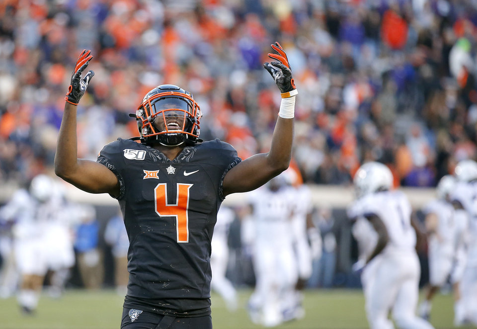 Photo - Oklahoma State's A.J. Green (4) celebrates in late in the fourth quarter during the college football game between the Oklahoma State University Cowboys and the TCU Horned Frogs at Boone Pickens Stadium in Stillwater, Okla.,  Saturday, Nov. 2, 2019. OSU won 34-27. [Sarah Phipps/The Oklahoman]