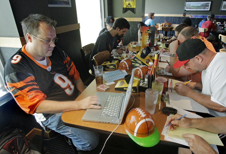 Photo - FILE - This Aug. 30, 2010 file photo shows Brian Sherman, left, using his laptop to record moves in his team's fantasy football draft, at a Buffalo Wild Wings restaurant in Cincinnati. As NFL owners and players wrestle over how to split $9.3 billion in revenue, pro football's lockout has already cut into the widely popular, $800-million per year fantasy football industry.  The pastime's popularity has become far more visible the past few years, with high profile players like Maurice Jones-Drew bragging about drafting themselves, a cable sitcom called