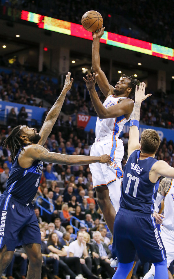 Photo - Oklahoma City's Jerami Grant (9) shoots against Dallas' DeAndre Jordan (6) and Luka Doncic (77) during an NBA basketball game between the Oklahoma City Thunder and Dallas Mavericks at Chesapeake Energy Arena in Oklahoma City, Monday, Dec. 31, 2018. Photo by Nate Billings, The Oklahoman