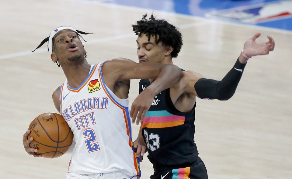 Photo - Oklahoma City's Shai Gilgeous-Alexander (2) tries to get around San Antonio's Tre Jones (33) of the NBA basketball game between the Oklahoma City Thunder and the San San Antonio Spurs at the Chesapeake Energy Arena, Wednesday, Feb. 24, 2021. [Sarah Phipps/The Oklahoman]