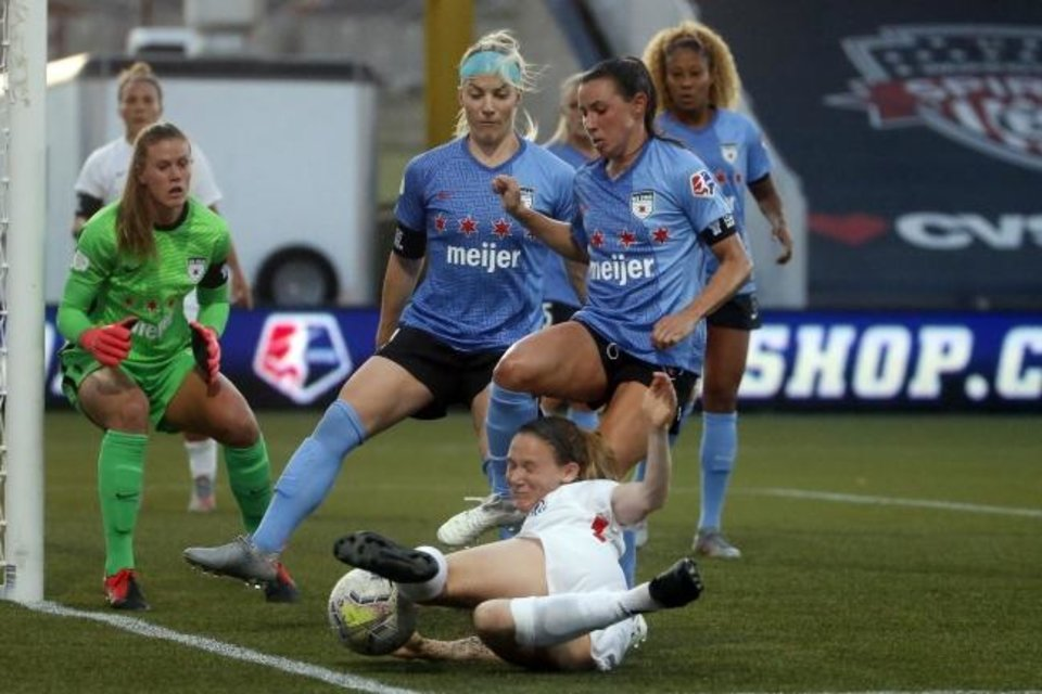 Photo -  OL Reign's Kristen McNabb slides after the ball as Chicago Red Stars' Julie Ertz, center, and Vanessa DiBernardo, right, defend Saturday in the quarterfinals of the NWSL Challenge Cup. The women's soccer league was the first professional team sports league in North America to return to action after the coronavirus shutdown. [AP PHOTO/RICK BOWMER]