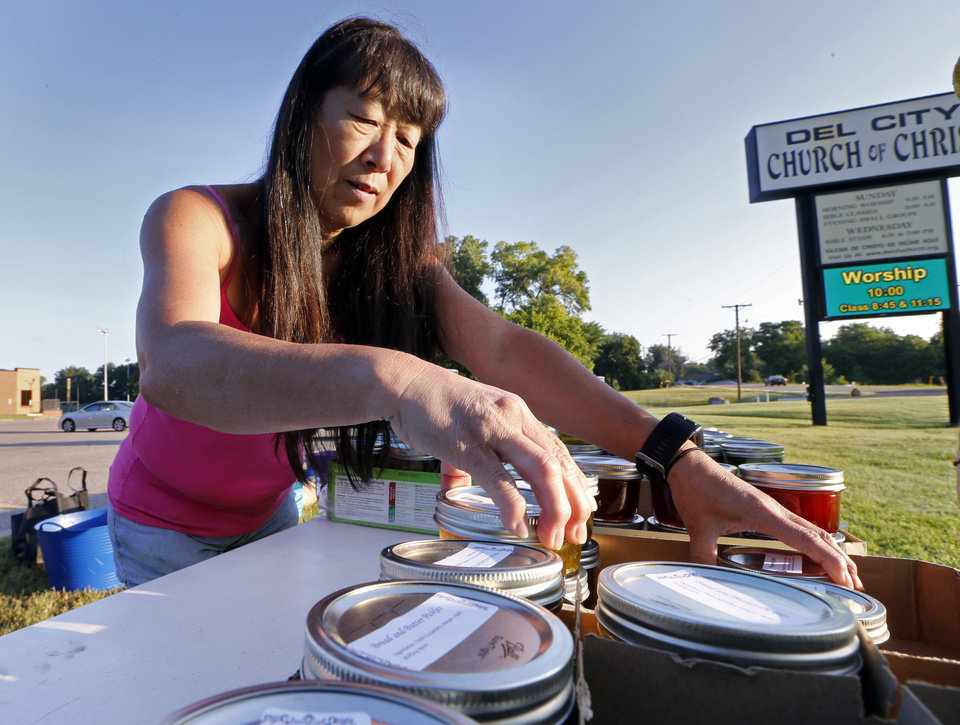 Photo -  Del City Church of Christ member Sandy Yoon helps distribute pickles she made from produce grown at the church's extensive community garden. [Photo by Steve Sisney, The Oklahoman]