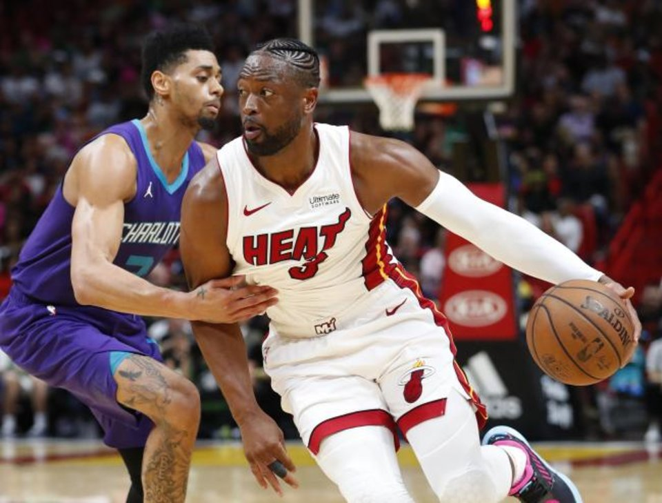 Photo -  Miami guard Dwyane Wade, right, drives past Charlotte's Jeremy Lamb during the Heat's 93-75 win over the Hornets on Sunday. Wade will likely play his final game in Oklahoma City on Monday night. [AP PHOTO/WILFREDO LEE]