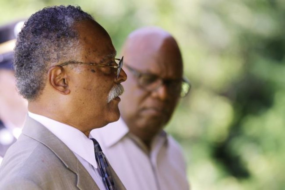 Photo -  Rev. Dr. M.L. Jemison, senior pastor of St. John Missionary Baptist Church, right, listens to Andre' L. Head of The Coltrane Group speak at the memorial service for World War I veteran U.G. Moore Tuesday at Trice Hill Cemetery. [DOUG HOKE/THE OKLAHOMAN]
