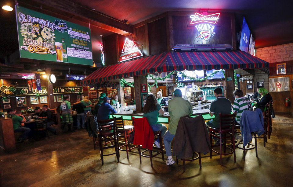 Photo - People drink inside O'Connell's Irish Pub and Grille on St. Patricks Day in Norman, Okla., Tuesday, March 17, 2020. O'Connell's was following the restrictions at the time to have no more than 50 people gathered together and limited the number of customers allowed in at once. [Nate Billings/The Oklahoman]