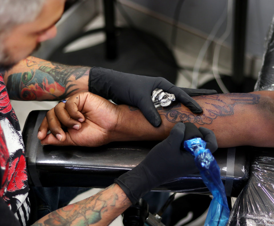Photo - THE OK Magazine. Drew Shurtleff, owner of The Ink Hub, applies a tattoo on the arm of a client, Monday, June 24, 2019. [Doug Hoke/The Oklahoman]