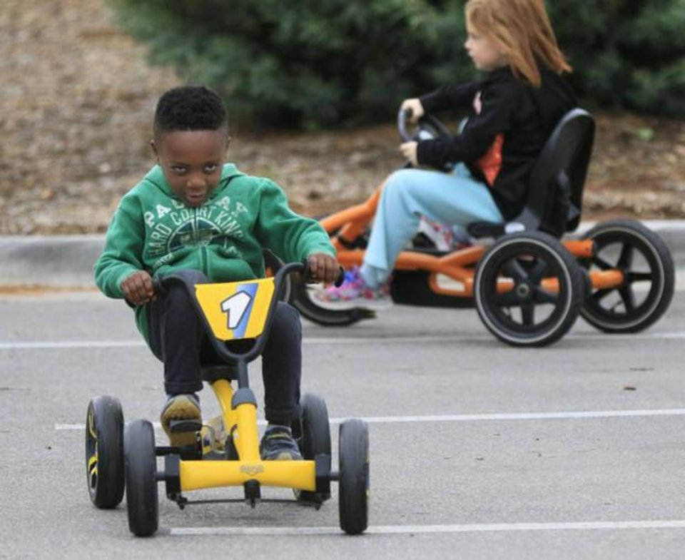 Photo -  Judah Shoemaker, 4, rides a cart over a safety course during Healthy Kids Day at Edmond's J.L. Mitch Park. [PHOTO BY PAUL HELLSTERN, THE OKLAHOMAN]