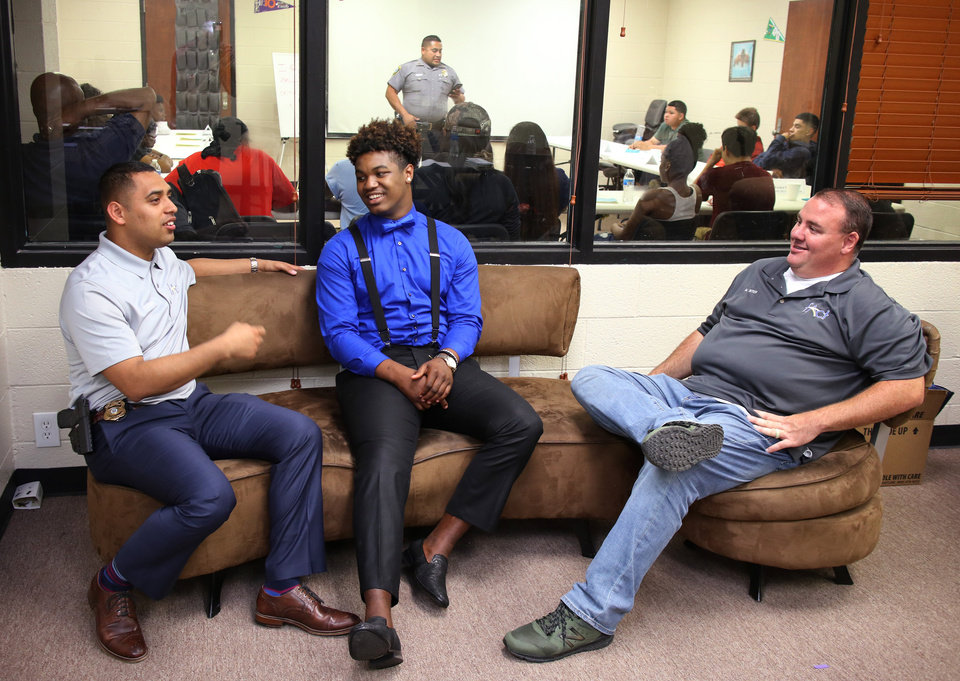 Photo -  Oklahoma City police Sgt. Tony Escobar, left, and police Master Sgt. Matt Sites, at right, talk with Damian Byest, of Moore, a graduate of a the police department's new Juvenile Intervention Program at Hathaway Park Police Athletic League. [Photo by Doug Hoke, The Oklahoman]