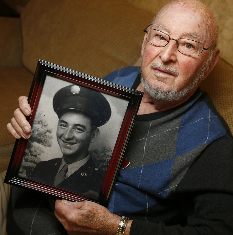 Photo -  Frank Sauter on Friday holds a photo that shows him after basic training. Sauter was exposed to mustard gas during experiments conducted on U.S. troops during World War II. [Photos by Nate Billings, The Oklahoman]