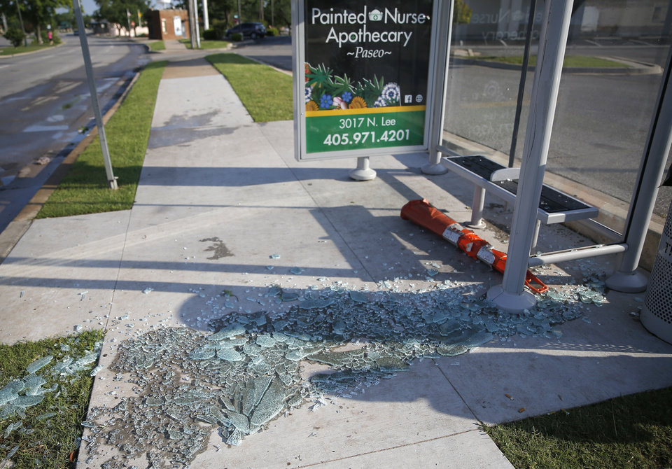 Photo - Shattered glass from a bus stop lies on the ground at NW 23rd St. and Classen after an apparent tornado moved through the area in Oklahoma City, Sunday, May 26, 2019.  [Sarah Phipps/The Oklahoman]