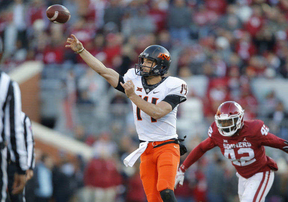 Photo - Oklahoma State's Taylor Cornelius (14) throws a pass during a Bedlam college football game between the University of Oklahoma Sooners (OU) and the Oklahoma State University Cowboys (OSU) at Gaylord Family-Oklahoma Memorial Stadium in Norman, Okla., Nov. 10, 2018.  Photo by Bryan Terry, The Oklahoman