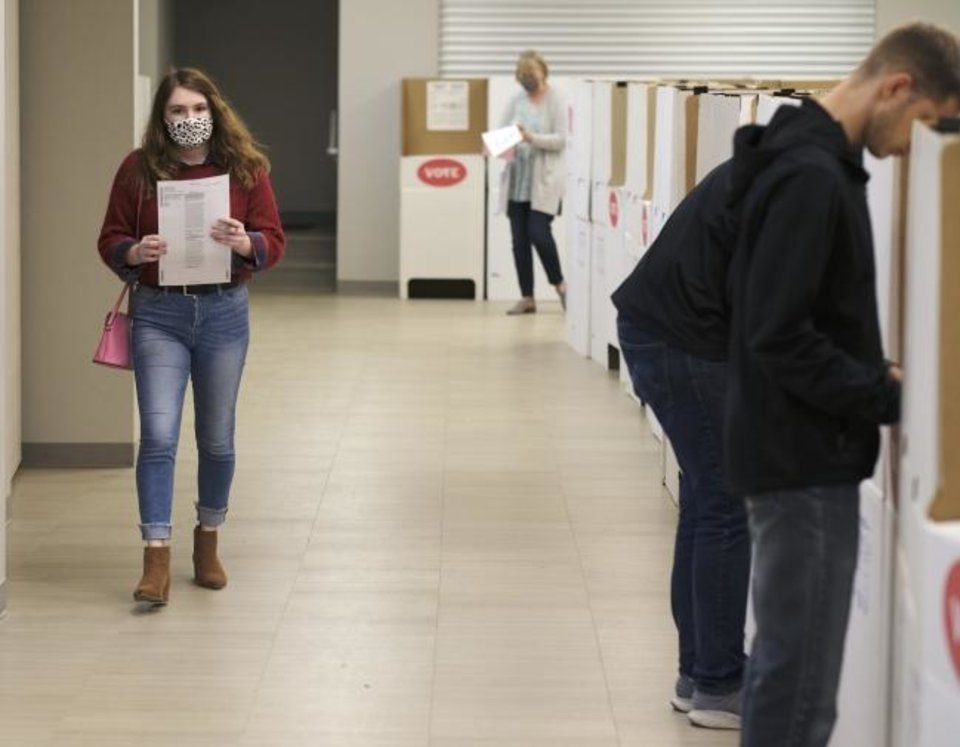 Photo -  First-time voter Michyla Armstrong walks to a voting cubicle. The 19-year-old Edmond resident waited in line for about four hours to vote early at the Edmond Church of Christ, Friday, October 30, 2020. [Doug Hoke/The Oklahoman]