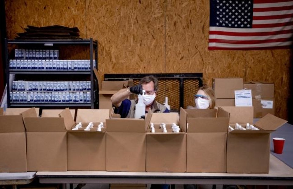 Photo -  Tim and Emma Haley box up bottles of Okie Clean hand sanitizer and all purpose cleaner at the Okie Clean warehouse. [Chris Landsberger/The Oklahoman]