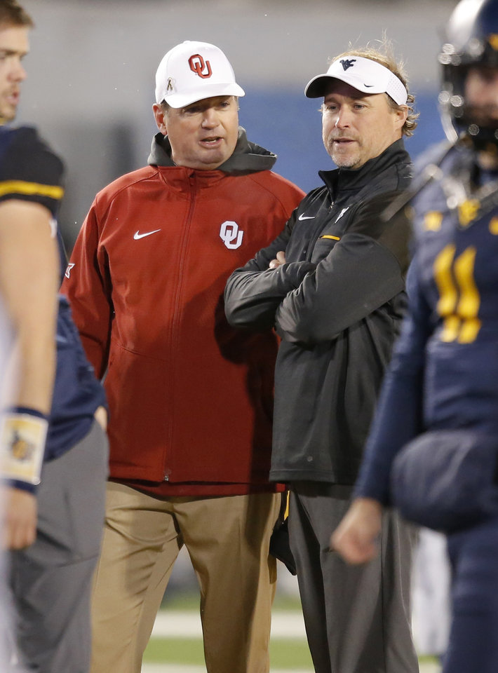 Photo - Oklahoma coach Bob Stoops and West Virginia coacg Dana Holgorsen meet before a college football game between the University of Oklahoma Sooners (OU) and and the West Virginia University Mountaineers (WVU) on Mountaineer Field at Milan Puskar Stadium in Morgantown, W. Va., Saturday, Nov. 19, 2016. Photo by Bryan Terry, The Oklahoman