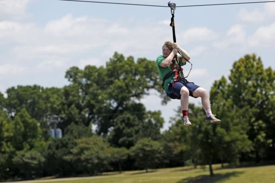 Photo -  Justus Prible, 16, zip-lines across the Oklahoma River on June 23 at Riversport Adventures in Oklahoma City. [Paxson Haws/The Oklahoman]