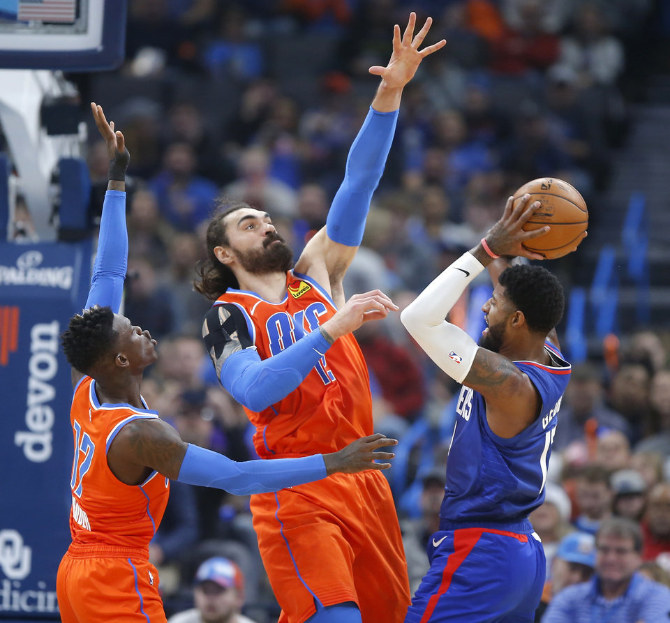 Photo - Oklahoma City's Steven Adams (12) and Dennis Schroder (17) defend LA's Paul George (13) during an NBA basketball game between the Oklahoma City Thunder and the LA Clippers at Chesapeake Energy Arena in Oklahoma City, Sunday, Dec. 22, 2019. [Bryan Terry/The Oklahoman]