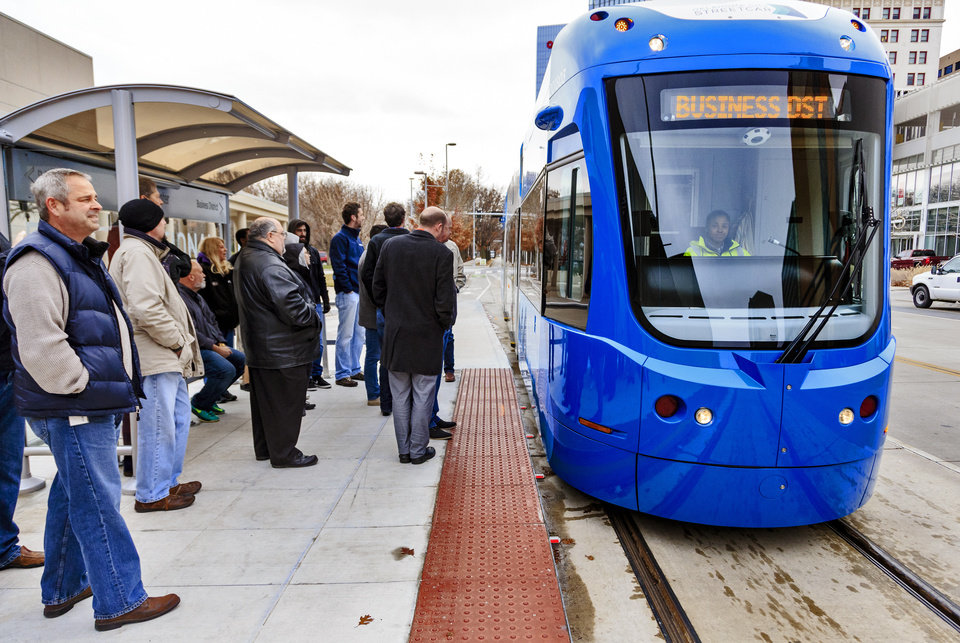 Photo - People wait to board the streetcar at the Century Center stop for a free ride during the grand opening celebration day of the Oklahoma City streetcar system in downtown Oklahoma City, Okla. on Friday, Dec. 14, 2018. Photo by Chris Landsberger, The Oklahoman