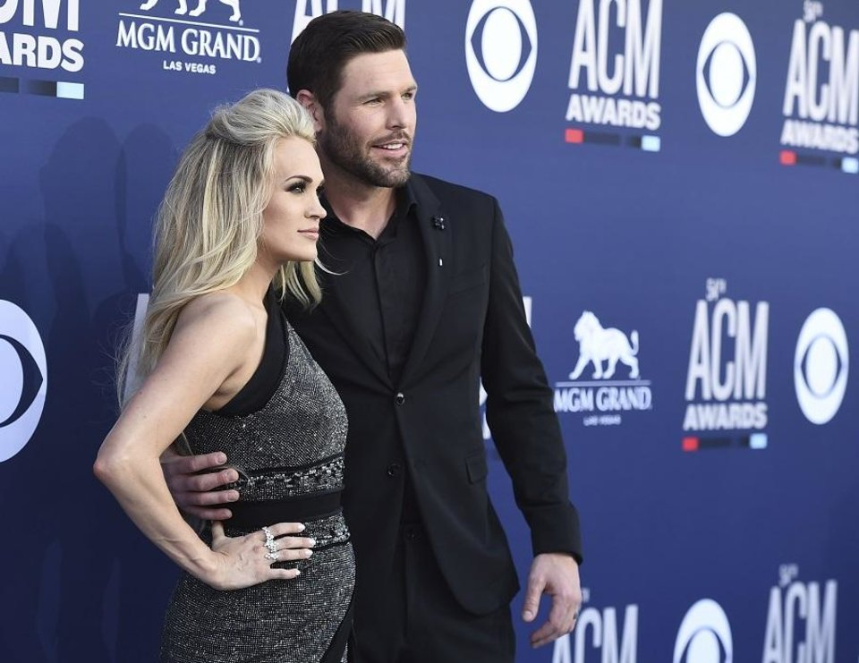 Photo - Carrie Underwood, left, and Mike Fisher arrive at the 54th annual Academy of Country Music Awards at the MGM Grand Garden Arena on Sunday, April 7, 2019, in Las Vegas. (Photo by Jordan Strauss/Invision/AP)