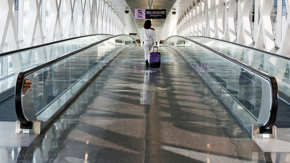 Photo -  A traveler walks with her luggage across a nearly empty skyway bridge at Logan Airport Friday in Boston. With the coronavirus surging out of control, the nation's top public health agency pleaded with Americans not to travel for Thanksgiving and not to spend the holiday with people from outside their household. [AP Photo/Michael Dwyer]