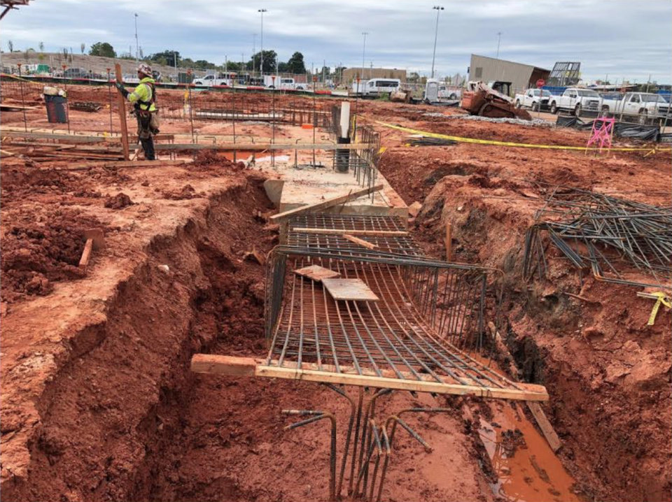 Photo -  Steel-reinforced foundation beams are poured in trenches. Across Robinson Avenue from the convention center, construction of the MAPS 3 downtown park continues in the background in this Oct. 16 view. [Populous/GSB/City of Oklahoma City]