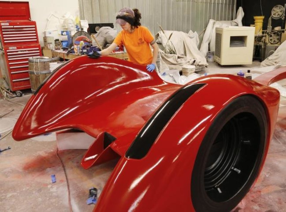Photo -  Amanda Robles conditions and polishes the bright red finish on the front end of the concept car for this year's auto show. Work on the car is being completed in a warehouse that is part of Taylor Foam.  As part of the 2019 OKC Auto Show, organizers held a competition for the design and creation of a concept car, the first to be commissioned by an auto show. Robles is an artist with Taylor Foam.  [Jim Beckel photos/The Oklahoman]