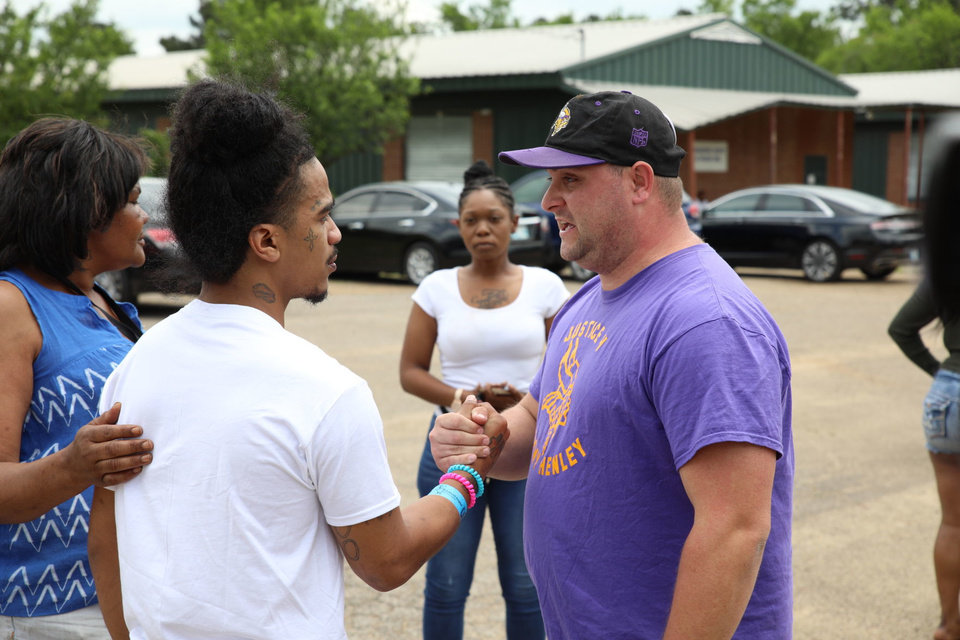Photo -  A man speaks with Quin Jacobs (left) during a protest in Hugo after three of Jacobs' children were injured Friday in an officer-involved shooting. [HARRISON GRIMWOOD/Tulsa World]