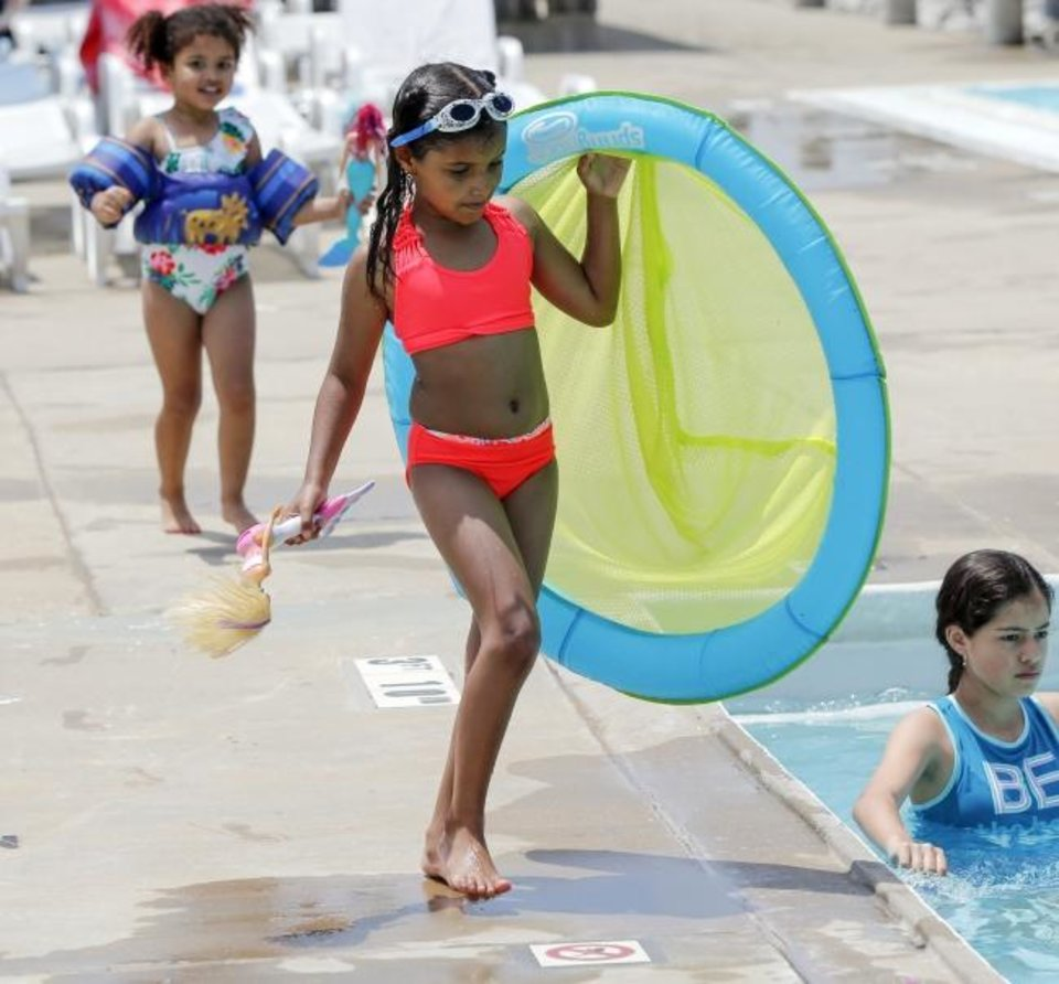 Photo -  Brooklyn Rowland, 7, middle, walks to the water in front of sister Zuri, 3, Saturday at Will Rogers Family Aquatic Center.