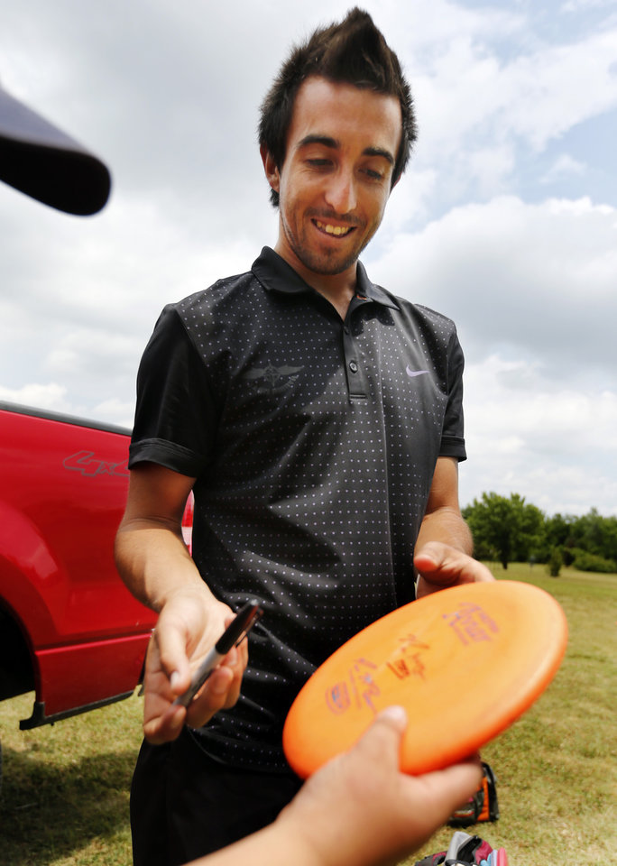 Photo -  Paul McBeth, two-time disc golf world champion and the highest-ranked disc golfer in the world, signs a disc for a fan at the 36th annual Pro/Am at Northeast Lions Park in Norman. PHOTO BY STEVE SISNEY, THE OKLAHOMAN   STEVE SISNEY -