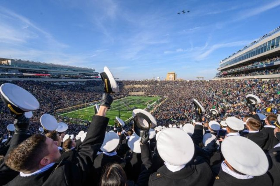 Photo -  United States Naval Academy midshipmen cheer as a formation of F/A-18 Super Hornet and E/A-18 Growler aircraft fly over before Navy's game last year at Notre Dame. The teams will not play each other this season for the first time in 95 years. [Matt Cashore-USA TODAY Sports]